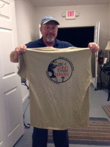 "Mike, holding a shirt that says, ""Take a Stand to Fight Hunger."" The shirt was given to him by a local church group, Heart of a Sportsman."
