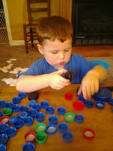 Playing a game of sorting bottle caps.