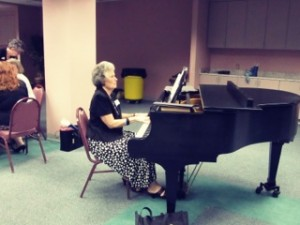 Nancy playing the piano for a program.