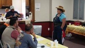 Sandi Hache, dressed as a farmer, explaining the rules for the chili cook-off.