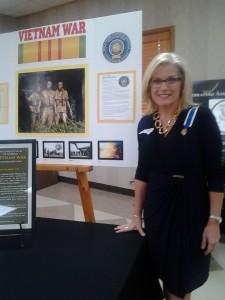 Elizabeth Marxwell Steele Chapter DAR Regent, Kim Edds, in front of a display about the Vietnam War.