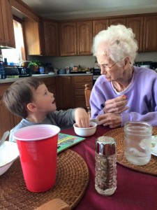My grandson, Garrett, having a conversation with his great-grandma, my mom.